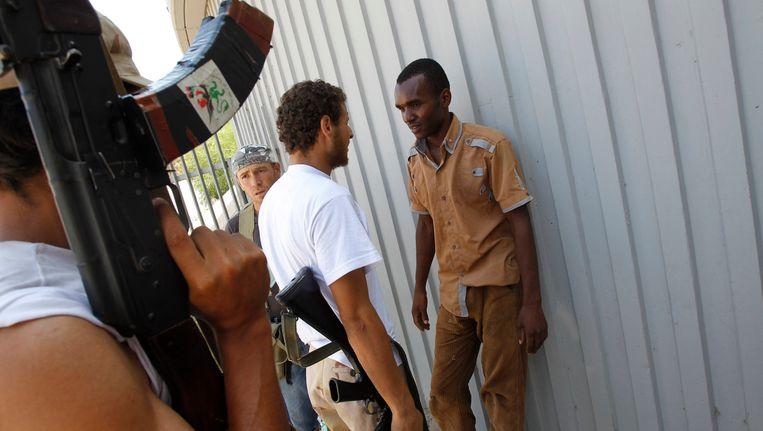 Een man die er van wordt verdacht een huurling voor Kaddafi te zijn, wordt aangehouden. Beeld REUTERS