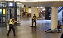 Beveiligingsbeeld: politieman Dave (links) houdt stationsterrorist Jawed onder schot terwijl hij in zijn portofoon praat.