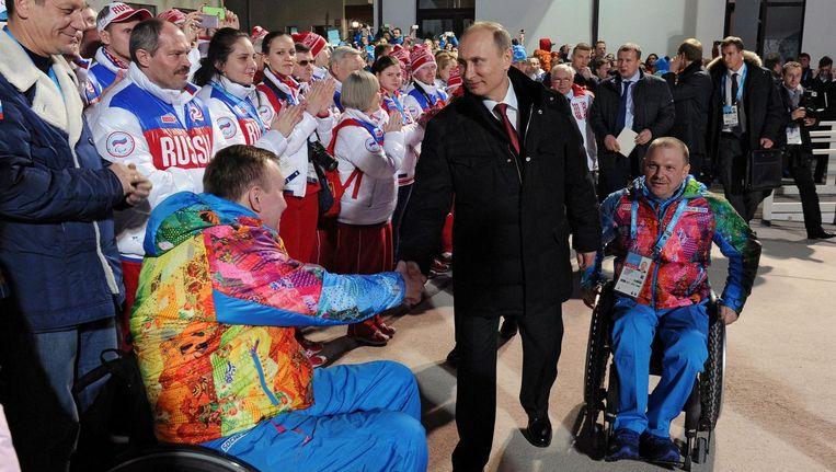 De Russische president Poetin schudt sporters de hand bij de Paralympische Winterspelen in Sochi, 2014 Beeld afp