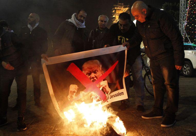 Palestijnse demonstranten verbranden een portret van Donald Trump in Bethlehem. Beeld AFP