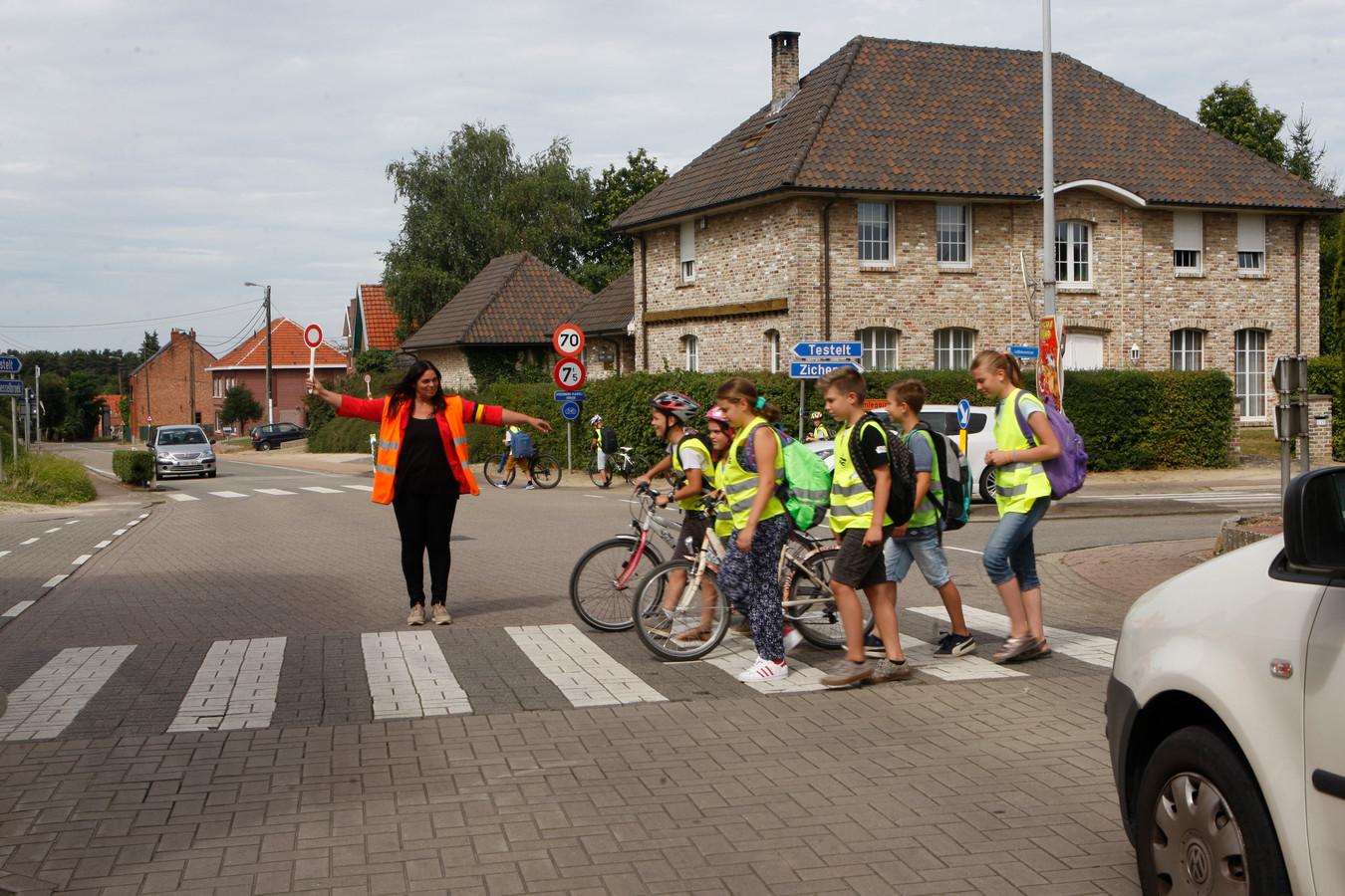 Leerlingen worden geholpen bij het oversteken van het kruispunt.