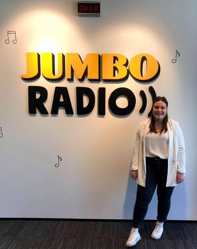 Romy Kieboom bij het logo van haar stageplek: Jumbo Radio.