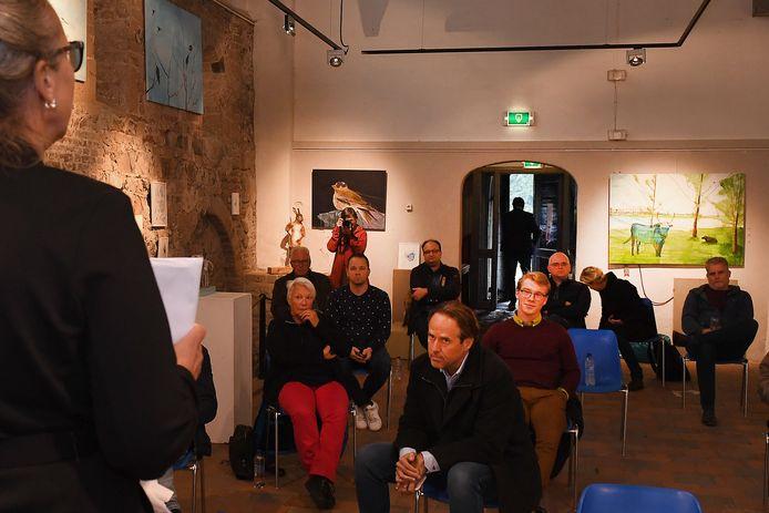 Frederique Bijl (links op de rug te zien, ziet hoe wethouder Theo Lemmen door de deuropening naar buiten stapt om niet meer terug te keren.