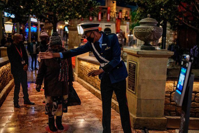 Een veiligheidsmedewerker dirigeert in Johannesburg mensen aan een casino naar een plek waar hun temperatuur eerst getest zal worden voor ze binnen mogen.