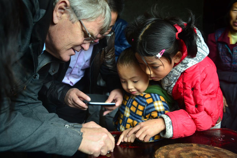 Twee Chinese kinderen luisteren geboeid naar Scott Rozelle.