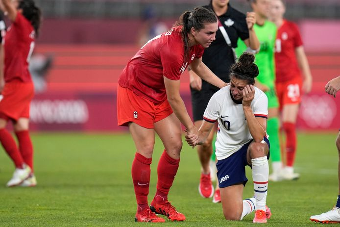 Vanessa Gilles (Canada) helpt de Amerikaanse voetbalster Carli Lloyd overeind.