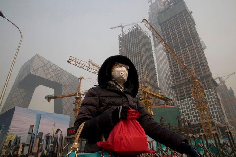 Een vrouw beschermt zich tegen de smog in Peking Beeld AP