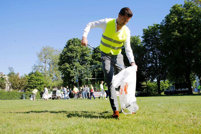Medewerkers van advocatenkantoor Wijn & Stael helpen mee met het opruimen van afval in het park Lepelenburg. Advocaat Stefan Holterman geeft het goede voorbeeld met vuilniszak en prikstok.