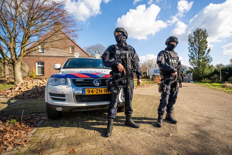 Agenten bewaken de omgeving van een hoveniersbedrijf in het Brabantse Neerkant nadat daar een drugslab is aangetroffen.  Beeld Bert Jansen