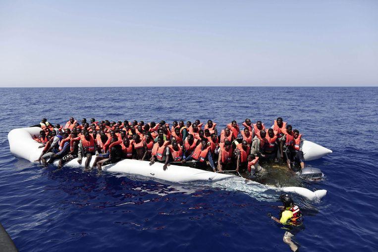 Een rubberboot met 304 vluchtelingen/migranten aan boord voor de Libische kust. Beeld EPA
