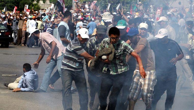 Morsi-aanhangers dragen een man die gewond is geraakt tijdens clashes met het leger. Beeld ANP