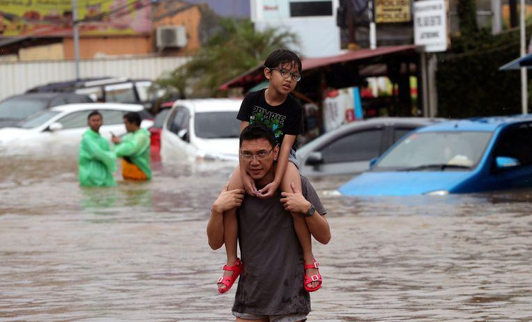 Een man waadt met een jongen op zijn nek door het oprukkende water in het district Jatibening in Oost-Jakarta. Beeld AP