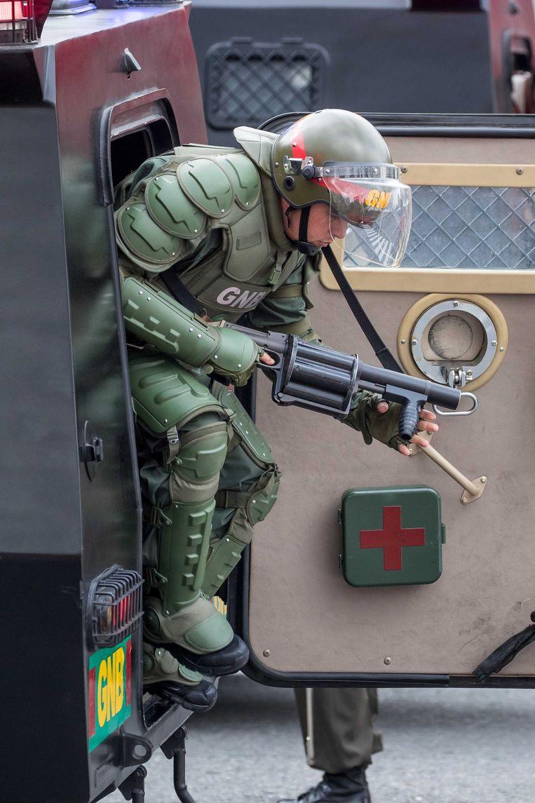 Een Venezolaanse soldaat springt uit een auto na een mogelijke aanslag op president Maduro. Beeld EPA