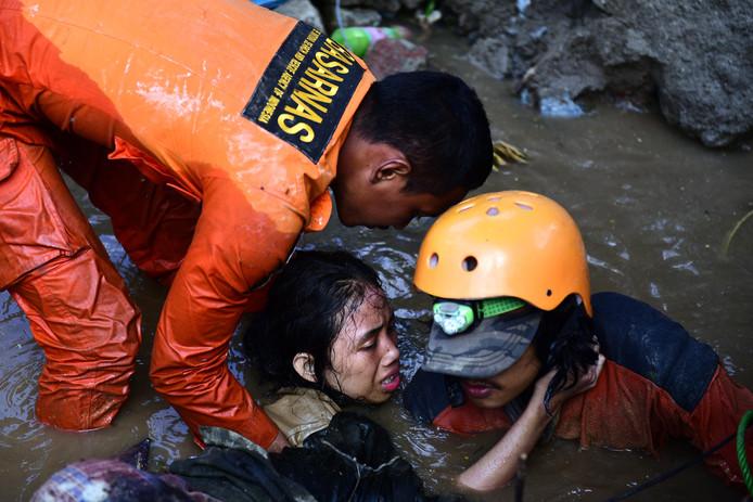 Reddingswerkers bevrijden een overlevende na de tsunami.