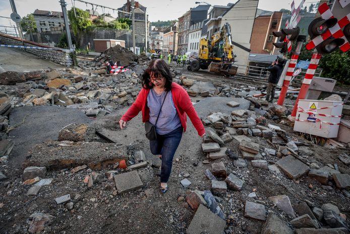 Een vrouw wandelt tussen het puin van de overstromingen in Dinant.