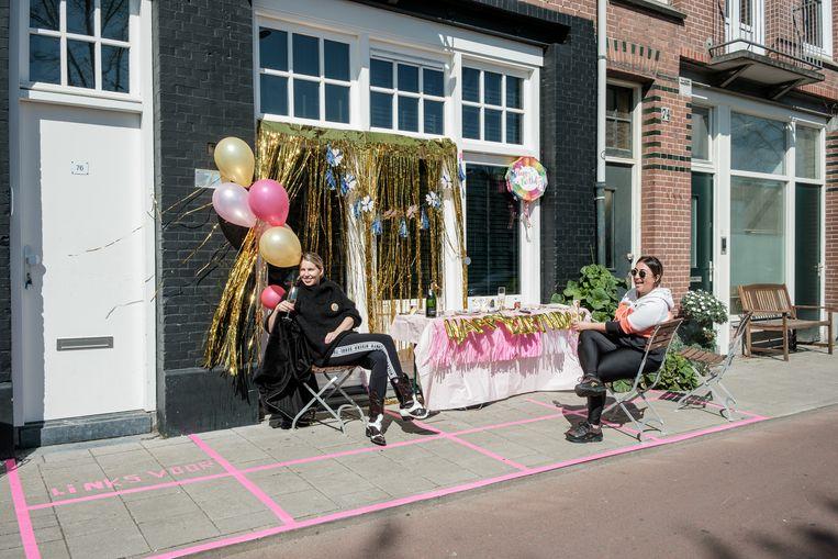 Malou (links), wonend aan de Houtmankade, vierde haar verjaardag op straat, met een raster voor zitplekken. Beeld Jakob Van Vliet