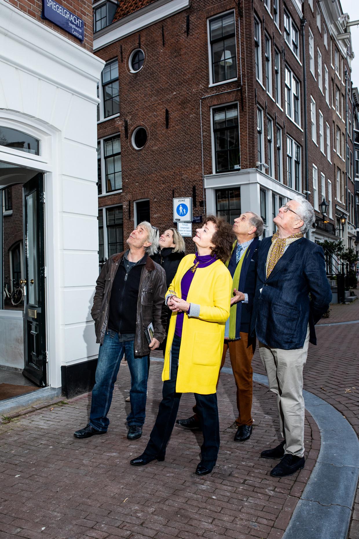 Tobias Snoep (links), Anneke Schat (in het geel), Rudolph Schat (achter haar) en Boudewijn Jansen (rechts) bekijken de gevelsteen na de onthulling. Beeld Nosh Neneh