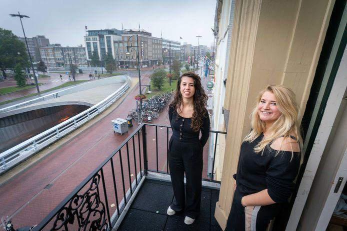 Lyan van Straten (rechts) en Emma Jansen op hun balkon, pal aan de Willemstunnel in Arnhem.