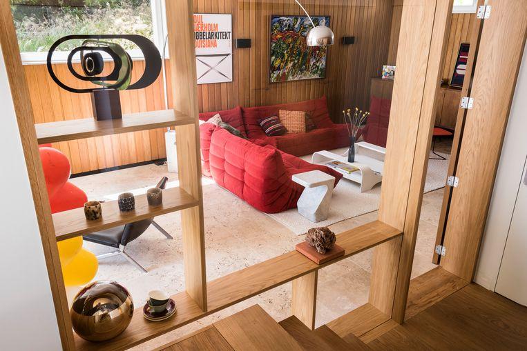In de living staat de rode sofa 'Togo' van Ligne Roset.De vloerlamp  'Arco' komt van Flos.  Beeld Verne