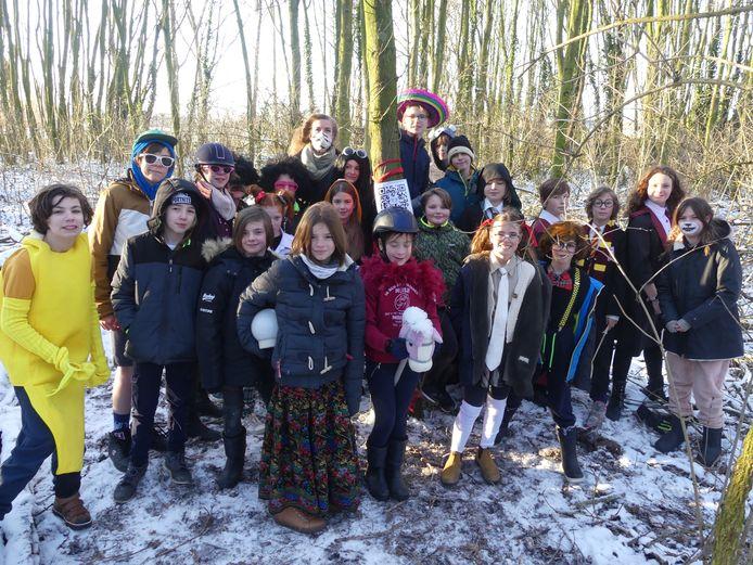 De leerlingen van De Sterrebloem aan één van de QR-codes in het bos. Die dag mochten ze ter gelegenheid van carnaval verkleed naar school komen.