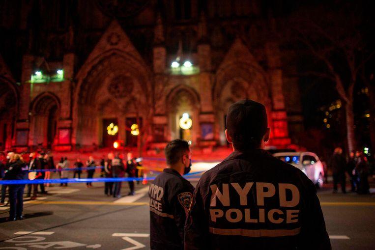 Agenten houden de wacht bij de kathedraal Saint John the Divine, in de wijk Harlem. Beeld AFP