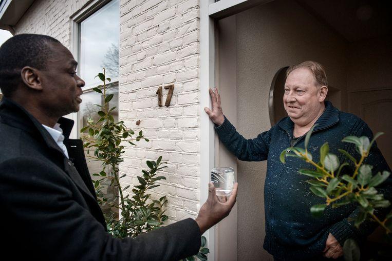 Schrijver Alphonse Muambi en Oranjenaar Gerard Wiechers.'Ik kom uit Afrika, en daar is een glas water een teken van gastvrijheid.'  Beeld Eric De Mildt