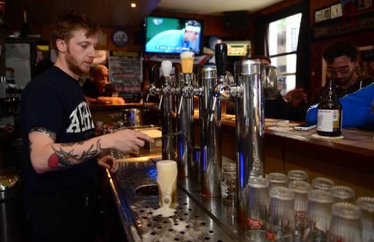 Barman Stijn Deweerdt van volkscafé Marengo tapt een 'ribbelke'. Rechts onderaan staat nog een hele voorraad. Toen ze hier het nieuws te horen kregen, hebben ze nog snel zo veel mogelijk exemplaren besteld.