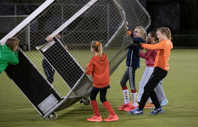 Jeugd van de hockeyclub in Geldermalsen rijdt het doel op zijn plek voor een trainingspartijtje.