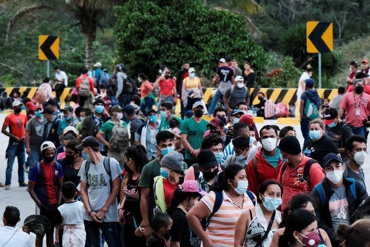 Mensen uit Honduras schuiven aan bij de grens met Guatemala.  Beeld REUTERS