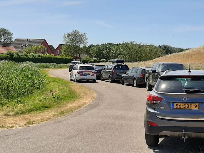 De politie neemt poolshoogte, maar bekeurt mensen niet die naast het parkeerterrein onderaan de dijk parkeren.