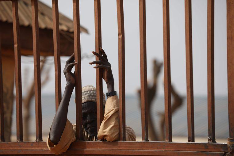 Een ouder wacht bij het hek van de school in Kankara, waar de ontvoering had plaatsgevonden. Beeld AFP
