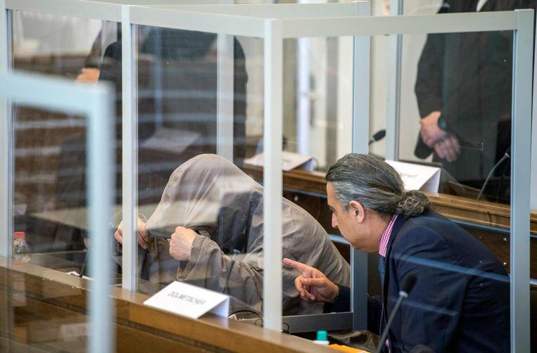 Eyad A. verbergt zich onder zijn capuchon voorafgaand aan zijnproces in Koblenz, West-Duitsland. Beeld AFP