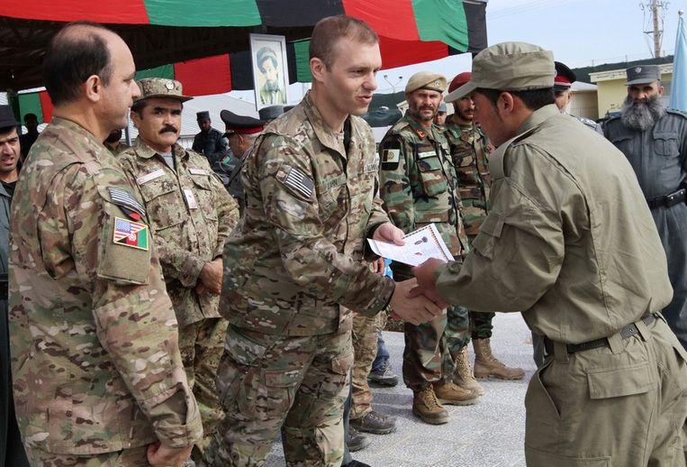 Niet de NAVO-agenten, maar de nieuwe Afghaanse agenten zijn vandaag het middelpunt van de belangstelling. De Amerikaanse NAVO-soldaat reikt een diploma uit aan de Afghaanse agent. Beeld epa