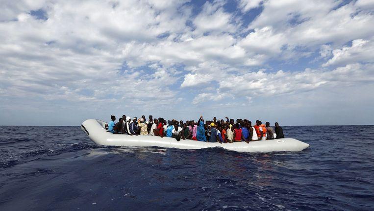 Een bootje met migranten dobbert op de Middellandse Zee voor de kust van Lampedusa. Beeld EPA