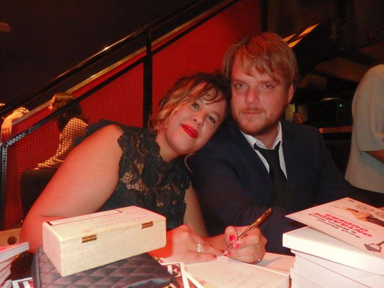 De ontaarde ouders Sarah Sluimer en Willem Bosch, druk aan het signeren. Sarah, na de derde fotopoging: 'Willem, kijk nou even in de lens!' Beeld Schuim