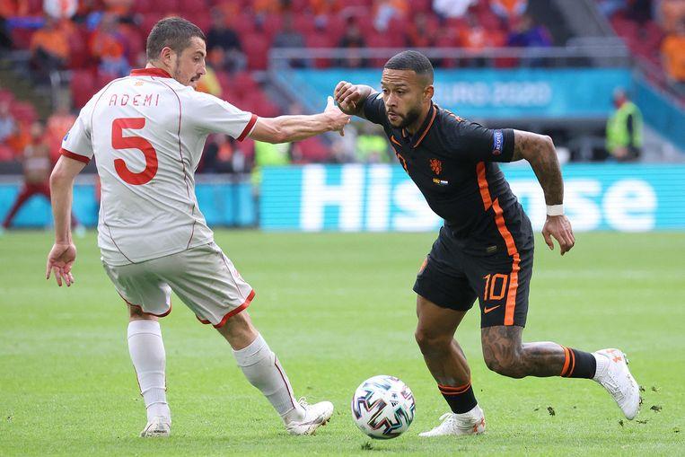 Middenvelder voor Noord-Macedonië Arijan Ademi (L) and Oranje-aanvaller Memphis Depay. Beeld AFP