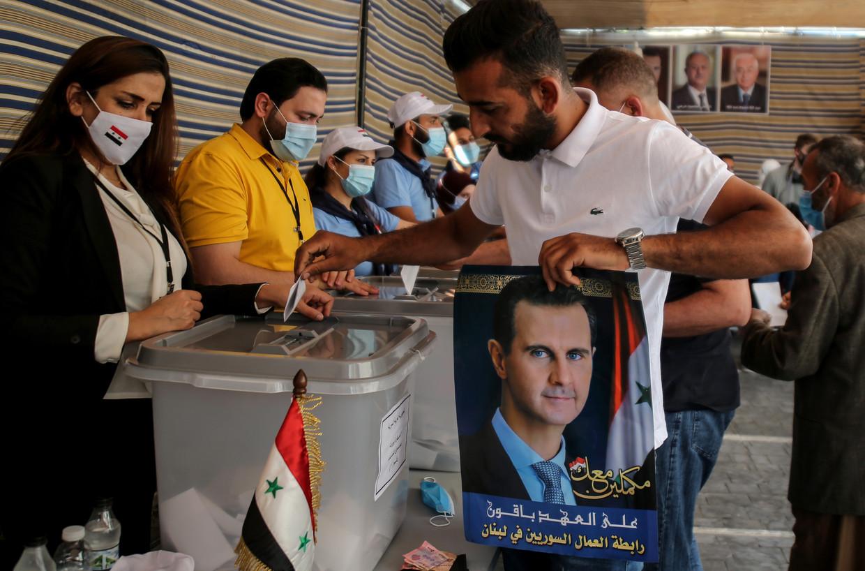 Een stembureau in het Libanese Beiroet. Een Syrische vluchteling brengt zijn stem uit, in zijn handen een steunbetuiging aan president Assad. 'Die posters zijn alleen voor de show. Als je in het stemhokje staat, kun je stemmen op wie je wilt.' Beeld EPA