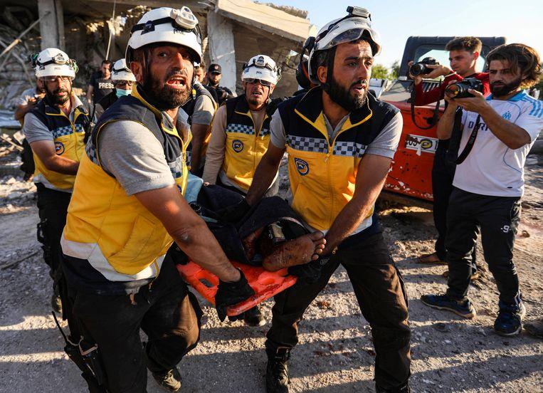 Reddingswerkers die bekendstaan als de Witte Helmen dragen in 2019 een slachtoffer weg na een luchtaanval op het dorp  Benin, in de noordwestelijke Syrische provincie Idlib.  Beeld Hollandse Hoogte / AFP