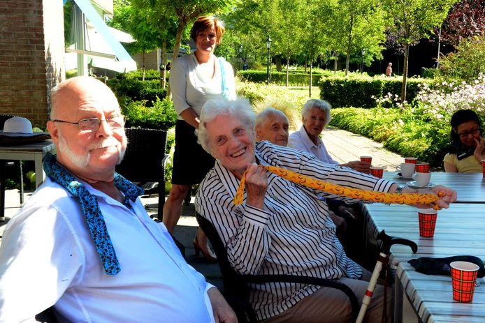 Bewoners Wim en Ankie van der Vange proberen de afkoelsjaal. Op de achtergrond kijkt Bernadette Sleurink toe.