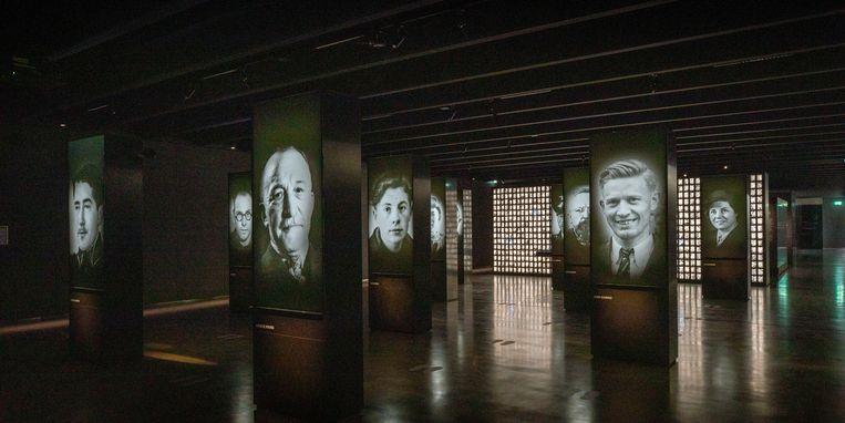 Foto's van sleutelfiguren uit de geschiedenis van Kamp Amersfoort. Onder elke grote foto is een lade uit te schuiven met extra informatie.  Beeld Werry Crone