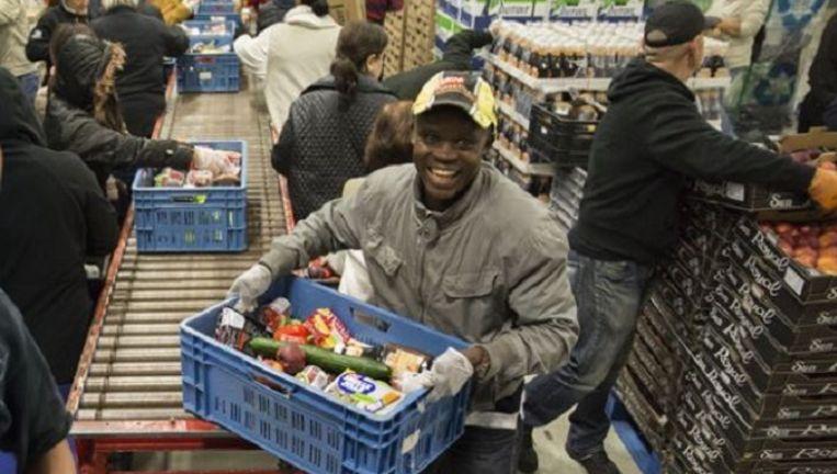 Vrijwilligers pakken voedselpaketten in. In de toekomst ook voor tweeverdieners? Beeld Arie Kievit