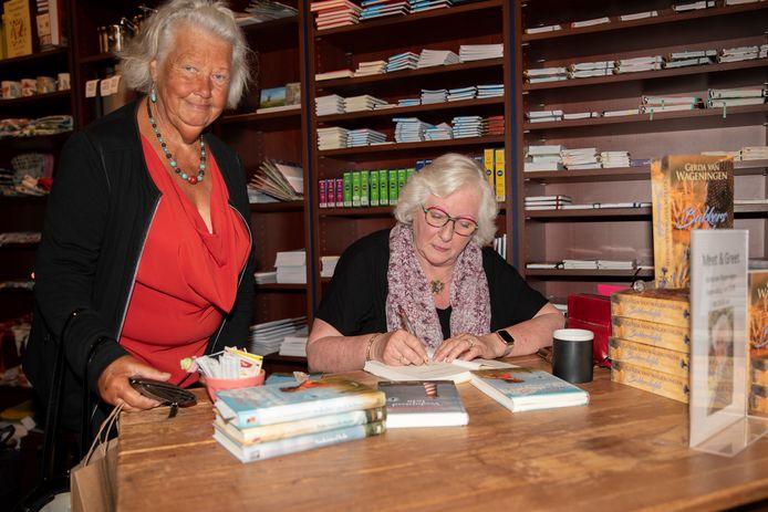 Gerda van Wageningen signeert haar boek voor Wil Vos bij Boekhandel de Vrieze in Zierikzee.