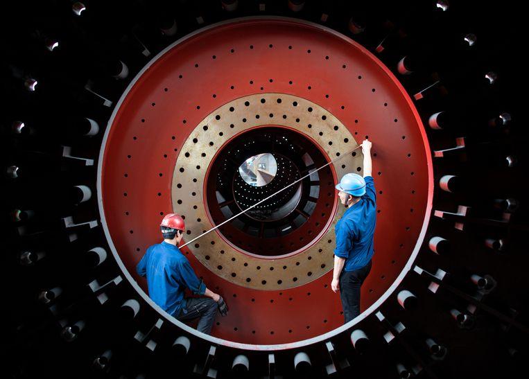Chinezen werken aan een onderdeel voor het 'Belt and Road'-initiatief: de moderne Chinese zijderoute die al bijna de wereld omspant.  Beeld Barcroft Media via Getty Images