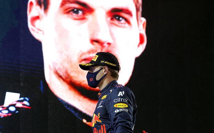 Max Verstappen na de podiumceremonie, met achter hem een levensgrote afbeelding van zichzelf.