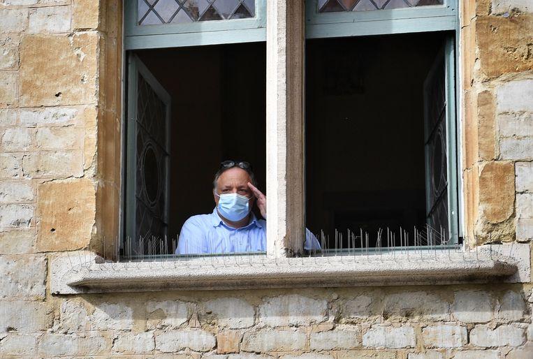 Viroloog Marc Van Ranst kijkt vanuit het gerechtsgebouw toe als Willem Engel arriveert. Beeld Marcel van den Bergh / de Volkskrant