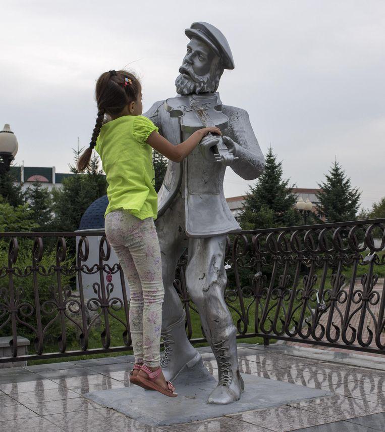 Een meisje speelt met het standbeeld van een vioolspeler van kunstenaar Vladislav Tsak. Beeld Yuri Kozyrev/ Noor