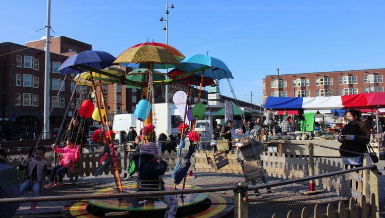De draaimolen vol paraplu's (je weet immers nooit) op de Mercatormarkt. Beeld Mildred Theunisz
