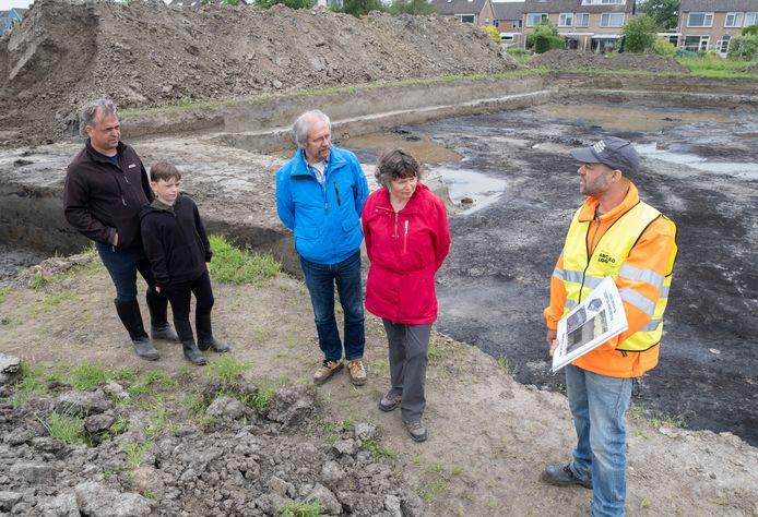 Archeoloog Bram Silkens (rechts) legt aan Wim en Pieter Huibregtse en Johan en Mineke de Visser uit hoe in de IJzertijd er geleefd werd in de omgeving van Serooskerke. Achter hen de afgraving.