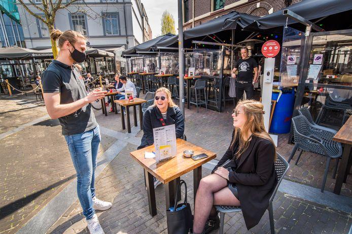 Annelies Kamp (midden) en Mares de Bruijn waren gisteren de eerste bezoekers van het terras van wijn en bierlokaal 't Hookhoes aan het Amaliaplein in Almelo.