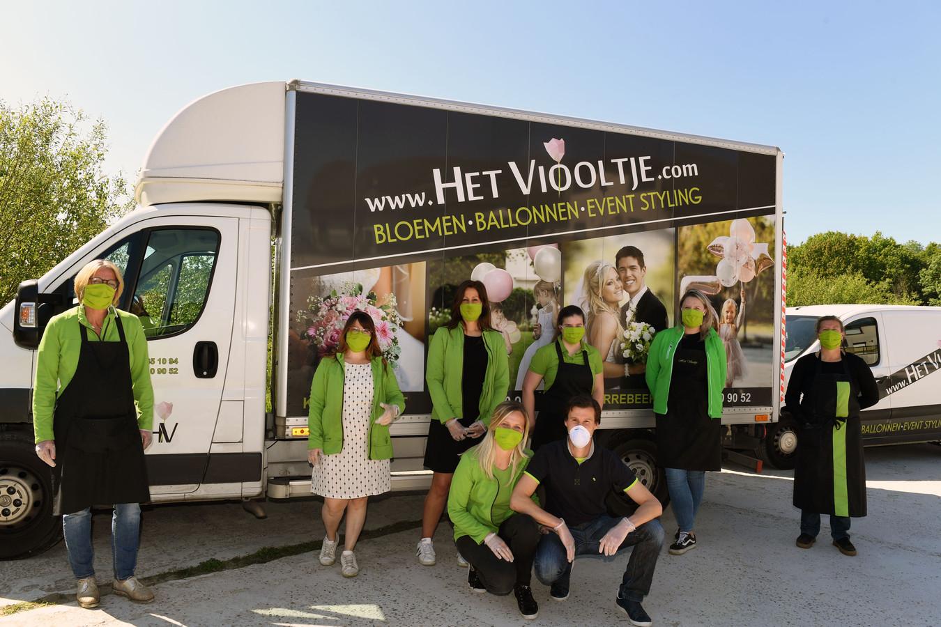 De crew van Het Viooltje voor een bestelwagen.